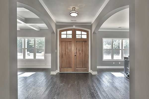 Beautiful foyer with hardwood floors, white trim and moldings, grey walls, large statement entry door, coffered ceiling and lots of windows.
