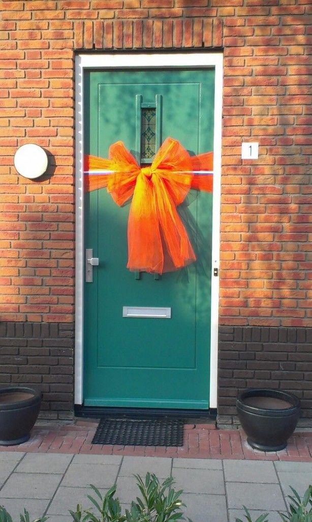 versiering voordeur. benodigdheden :  - 5 meter oranje tule. - 3 meter rood/wit/blauw lint 5 cm breed - spelden