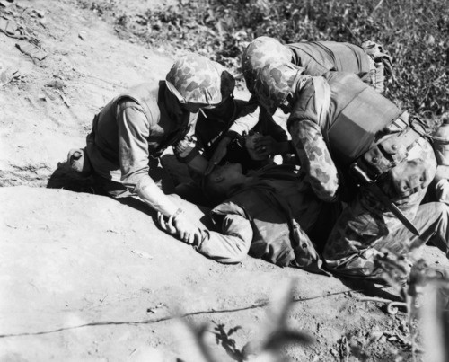 During the bitter fighting on Hook Ridge, the US Marines held back 800 Chinese soldiers. Sometime amidst the battle this Marine was wounded and his buddies stayed with him, giving him water while waiting for evacuation to a rear aid station, November 1952.