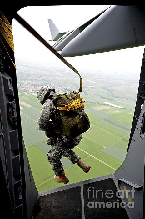A Paratrooper Executes An Airborne Jump, not too tight of a body position.No weapon no rucksack humm, cherry jump?