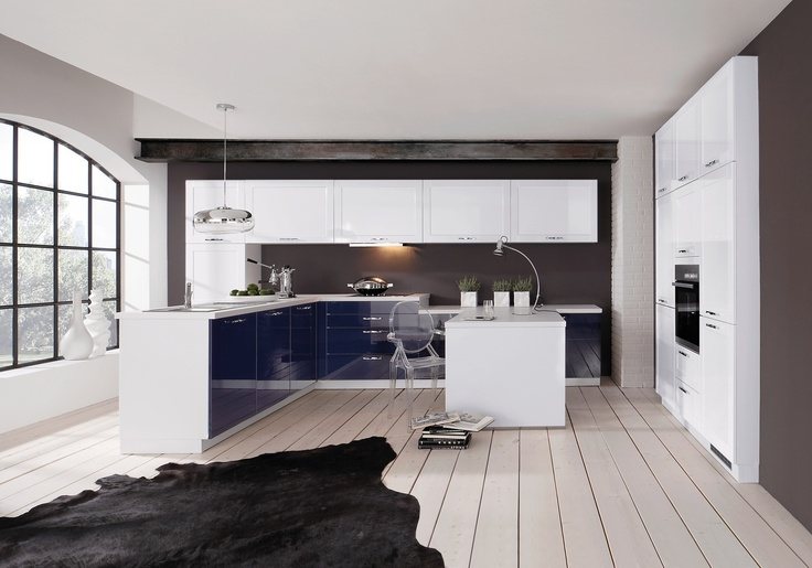 Im modernen Design präsentiert sich diese Küche mit einer eleganten Blau-Weiß-Kombination und edel glänzenden Oberflächen. Die weißen Wandschränke bieten viel Stauraum und werden durch die beigegraue Wandfarbe optimal in Szene gesetzt. Mit der weißen Lasierung erhält der Raum ein exklusives und zugleich gemütliches Ambiente, das durch den schwarzen Fellteppich unterstrichen wird. Dekorative Elemente wie die formschöne, silberne Deckenleuchte oder die großen Keramik-Vasen am Fenster runden…