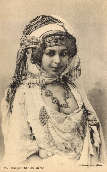 Staged photo of an Algerian girl in a rather fantastic mix of French and North African dress. The photographer, J.Geiser had a photography studio in Algers. If you look close you can see the tattoo between her eyes and on her chin.