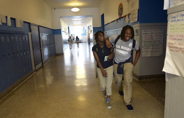 Perry Street Prep senior Christian Adams right walks through the school hallways with his best friend and girl's rugby team member Leondra Wright at...
