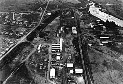 Aerial view above Kingston looking west over Kingston Power Station.shows railway line for coal deliveries,concrete pipe works, saw mill, ice works and Mologlo River backed up by the weir