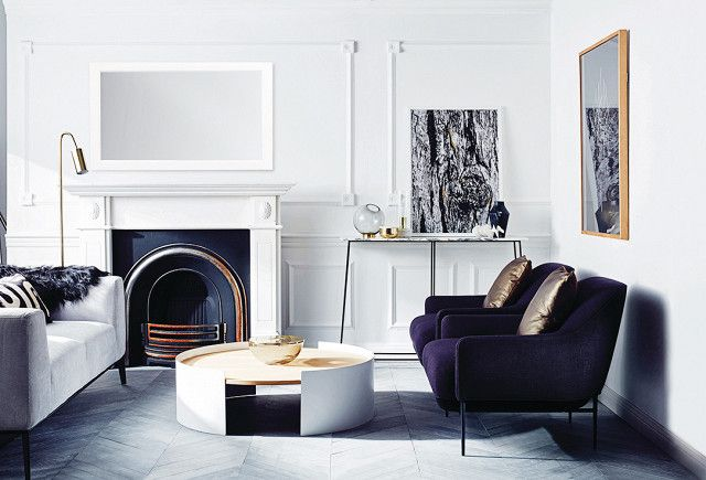 Swedish living space with a fireplace, matching purple velvet armchairs, and a gray armchair