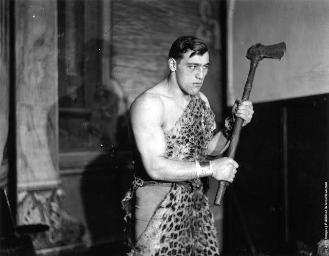 "Primo Carnera (1906–1967) the Italian heavyweight boxer and wrestler poses in a leopard skin to represent a cave-man at a ""Joy of Life"" Ball at the Royal Opera House, Covent Garden, London. 13th December 1929. (Photo by Topical Press Agency/Getty Images)"