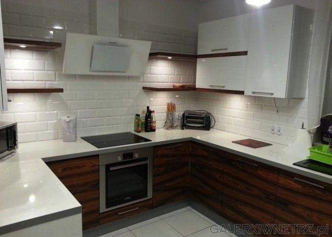 Elegancka, nowoczesna kuchnia z bieląi drewnem. Blat kuchenny jest biały, tak samo ...