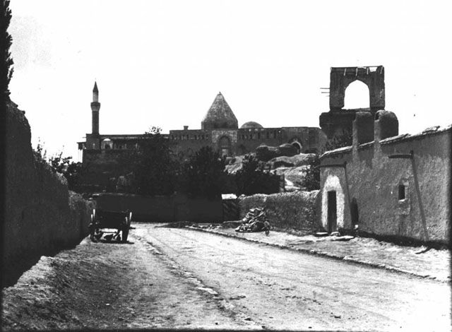 Alâeddin Camii - largest Selcuk mosque in Konya, taking seventy years to build and undergoing several modifications hence irregular form. Decagonal eastern turbe, western turbe is octagonal with dome. Kiosk in foreground is remains of defence tower converted into imperial residence in 13th C. Date taken: May 1905	 Photographer: Gertrude Bell Location: Konya - Turkey. Subject date: 12-13th C