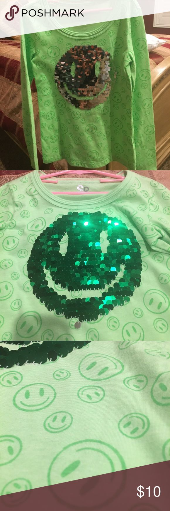Happy face shiny long-sleeves shirt reversible Adorable green happy face long sleeve shirt with shiny sequined happy face in the middle. Push all the sequence in One Direction and the happy faces silver. Push all the secrets in the opposite direction and the happy face is a beautiful emerald green. So much fun for your child!  Size girls 7/8 SO Shirts & Tops Tees - Long Sleeve