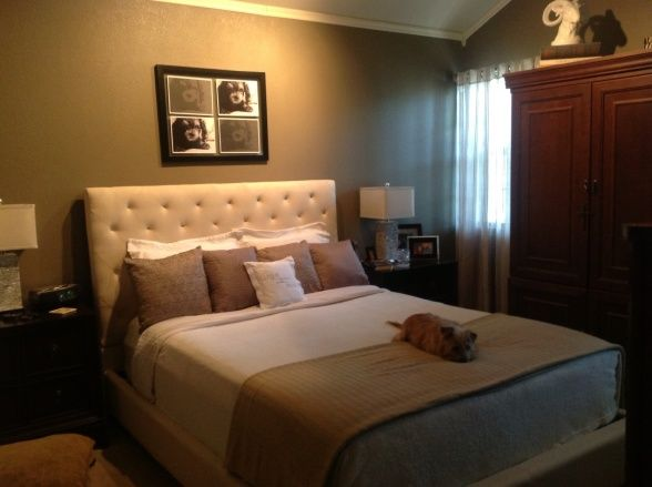 Small master bedroom feels warm, but not too feminine. A light headboard against darker walls with beige and dusty blue accents.