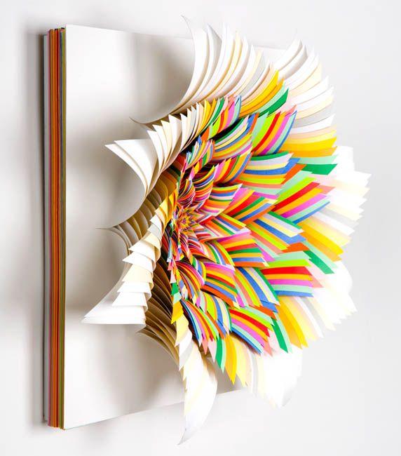 Jen Stark transforme des tas de papiers en sculpture d'art.    Elle fait des piles de feuilles de papier de couleur et elle y découpe différentes