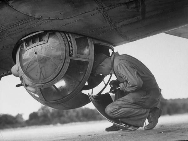 """Gunner Richard Getty checking out his machine gun ball turret which he named """"Ball of Fire"""" in the belly of his crew's B-17 Flying Fortress, September 1942"""