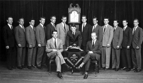 Skull & Bones Secret Society of Yale University (note: George H.W. Bush standing to the left of the clock.) Prescott Bush, George H.W. Bush, George W. Bush, and John Kerry are among their alumni. The society holds luciferian style rituals. Prescott Bush is said to have desecrated the grave of Geronimo and absconded with his skull (displayed front & center here). Reportedly,  the skull is still the possession of S&B.