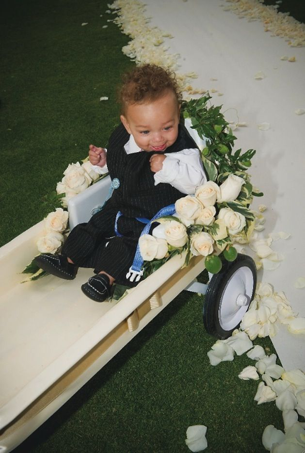 The couple's youngest ring bearer, who wore a pinstripe suit, was led down the white aisle runner in an ivory wagon decorated with vanilla roses and green vines. #ringbearer Photography: John Solano Photography. Read More: http://www.insideweddings.com/weddings/amanda-langston-and-nicholas-barnett/310/