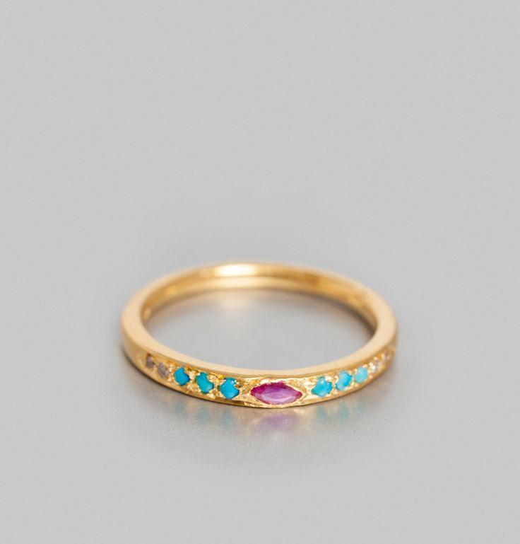 Bague en argent doré à l'or fin, incrustation de pierres aux nuances argentées et de turquoises autour d'une pierre centrale en losange couleur rubis.     Par l