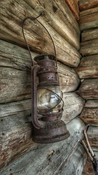 Old petrol lamp hanging on a wooden wall