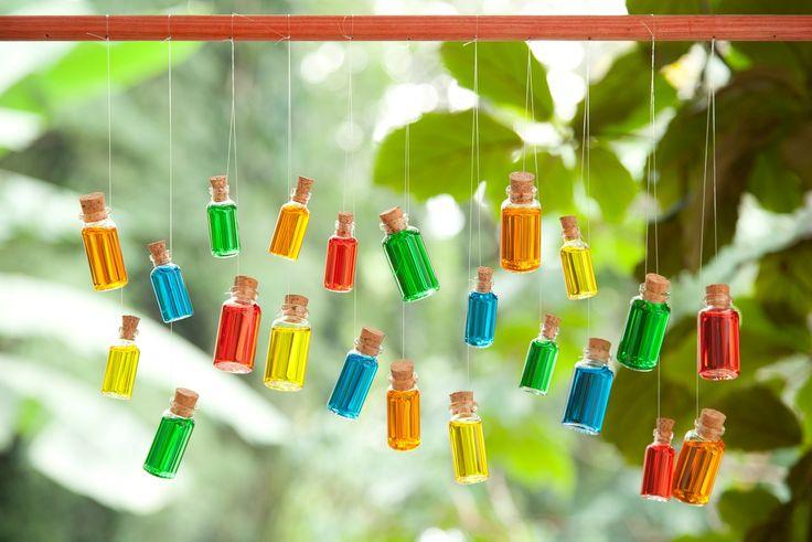 Para criar este efeito lindo, enchem-se pequenos frascos de vidro com água e corante alimentício. Em seguida, os vidrinhos com rolha foram presos a um fio de nylon suspenso com um cabo de vassoura. Ele é quase um móbile e fica incrível pendurado na janela!