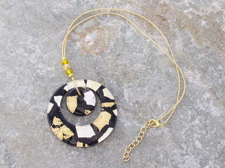 Pendente in vetro di Murano con doppia corona a forma di cerchio. La base è di colore nero con inserti in foglia d'argento e foglia d'oro.   La catena è fatta di perline in conteria, tutto in materiale anallergico (NICKE FREE).  Il cerchio è il simbolo dello spirito e dell'immaterialità dell'anima.