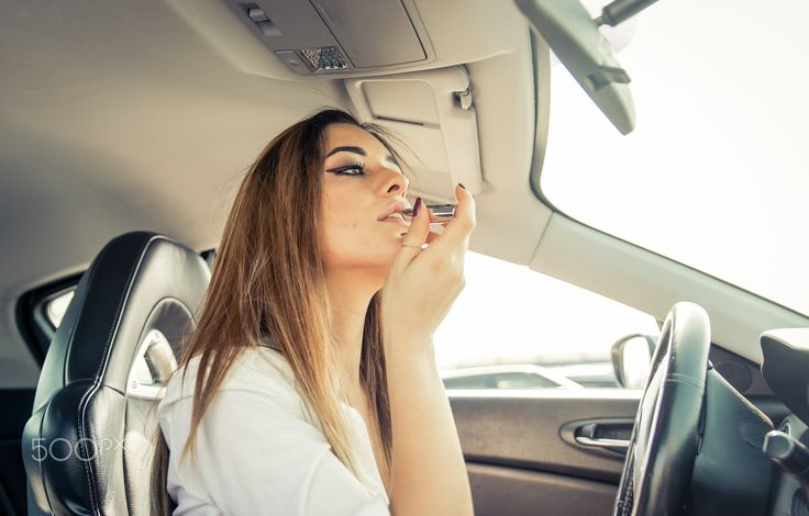 Woman putting lipstick in the car before date - Woman putting lipstick in the car before date