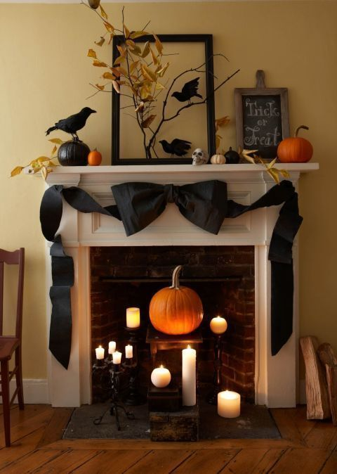 Tied in a Bow: Add a high-low Halloween theme to your mantel with pumpkins, crows, and a crepe paper bow. This easy Halloween decoration is the perfect example of turning Halloween crafts in decorations. Find more easy DIY Halloween decor and decoration ideas that are creepy and scary here. #halloweendecorationideas #diyhalloweendecorations #halloweentheme