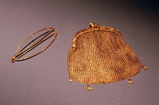 Artifacts include personal belongings of passengers and crew, such as a mesh purse.