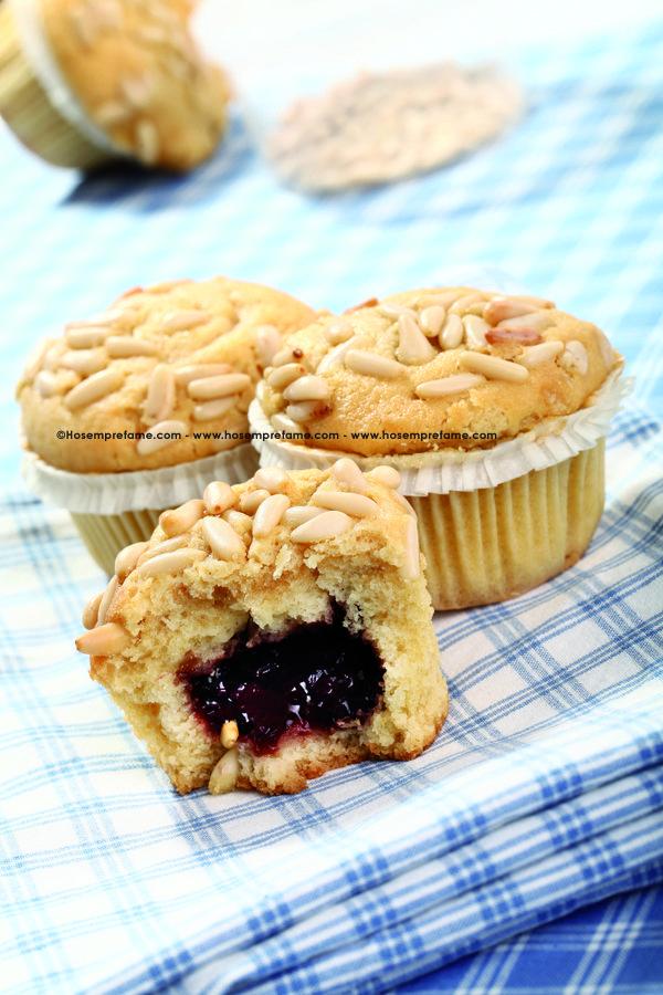 Questi dolcissimi muffin ai pinoli hanno un cuore di confettura a sorpresa. La nostra proposta suggerisce di usare quella fragola.