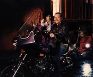 Prince Purple Rain Album cover photoshoot candid shot with movie staff member on his bike! Funny as Prince is holding a razor blade for some reason. This is a photo from the same session that the iconic cover was shot at - in the Burbank WB movie lot in fact... !