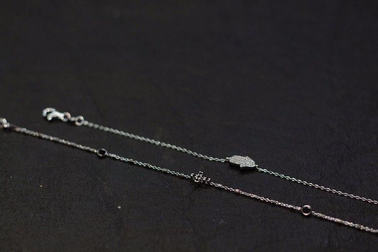 Bracciale in argento con croce di zirconi neri e bracciale con mano di Fatima con zirconi.