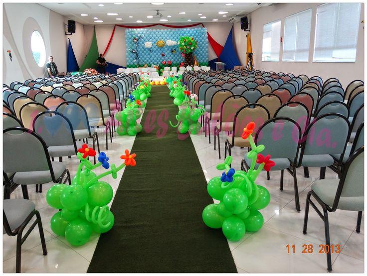 Corredor com esculturas de balão grama com flores e ao fundo mural com arvore e bichinhos