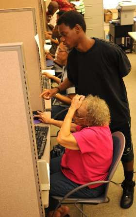Jay McCauley, 14, helps Minnie Cooper on the computer. As part of their sentences from a Teen Court diversion program, local teenagers do community service by teaching seniors how to use computers on the Edward Waters College campus. Don.Burk@Jacksonville.com