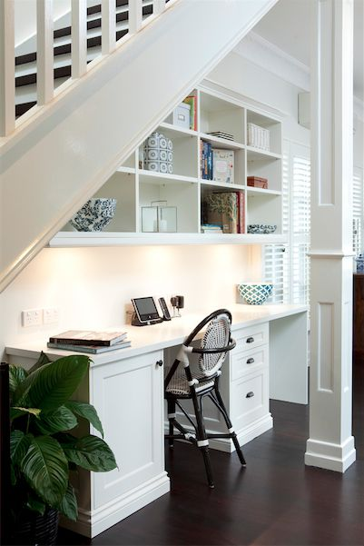 Great office space under the stairs. Dark hardwood floors and white builtin cabinetry and desk. Cool bistro chair, plantation shutters and peace lily. Source: Porchlight Interiors