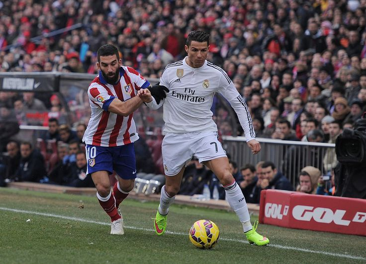 Cristiano Ronaldo of Real Madrid.is tackled by Arda Turan of Club Atletico de Madrid during the La Liga match between Club Atletico de Madrid and Real Madrid at Vicente Calderon Stadium on February 7, 2015 in Madrid, Spain.