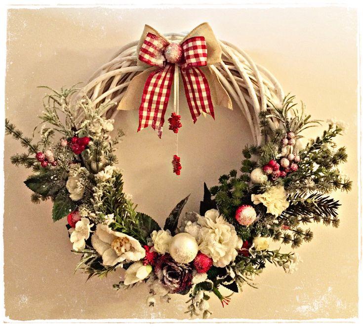 Ghirlanda natalizia creata a mano con fiori artificiali, palline di Natale e nastri.