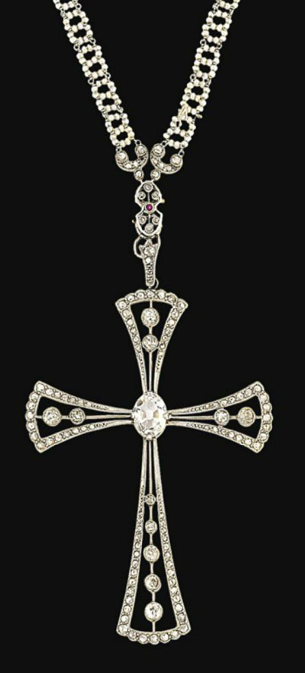 A Belle Epoque diamond and seed pearl pendant necklace  The cross pendant with old brilliant-cut diamond centre to openwork flared arms set with old brilliant-cut diamonds, to a ruby and diamond-set surmount and seed pearl fancy-link neck chain, circa 1920, pendant 9.0cm long