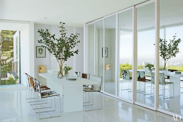 Sliding mirrored doors separate the dining room from the kitchen in architect and designer Daniel Romualdez's Los Angeles home | archdigest.com