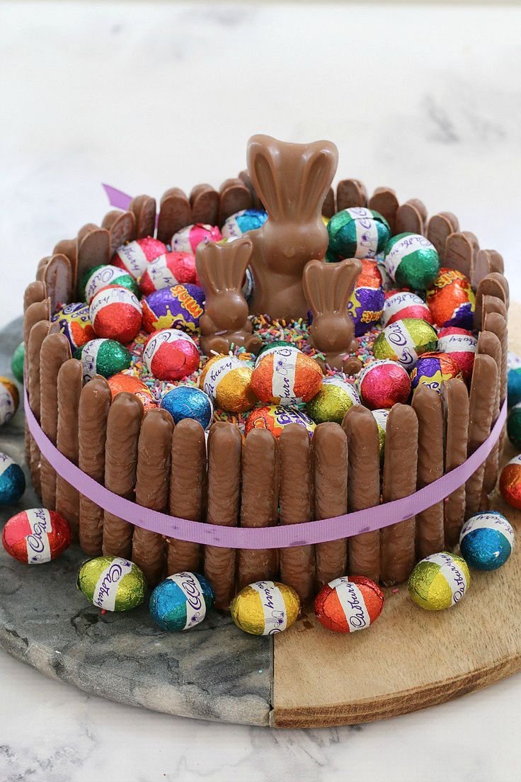 The ultimate cheats '15 Minute Chocolate Overload Easter Cake', made from a store-bought mud cake, covered in creamy milk chocolate frosting, piled high with sprinkles, chocolate easter eggs, creme eggs and Malteser bunnies, and surrounded by chocolate finger biscuits. This easter cake looks absolutely gorgeous and tastes even better… talk about a show stopping table centrepiece!     #easter #chocolate #cake #video #recipe #easy #15minutes #eastereggs #bunnies #sprinkles
