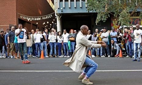 A man performs a street dance in front of crowds in Braamfontein, Johannesburg, South Africa