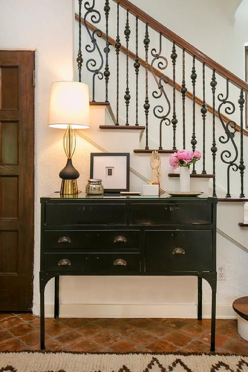 Mediterranean Foyer features a black industrial console table lining a staircase wall alongside a terracotta quatrefoil tile floor.