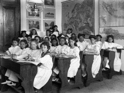 Een groep jonge Europese en Indische scholieren, in de schoolbanken van de Ursulinenschool te Bandoeng tijdens de aardrijkskundeles. 1880-1910.