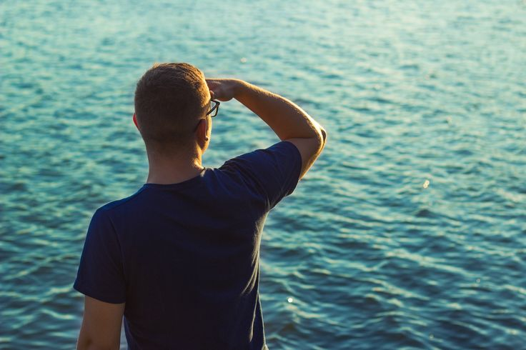Man looking at the horizon wearing Navy Explore T-Shirt by Pharos Apparel. This is men outfit. Yacht Style, Pier, Sea