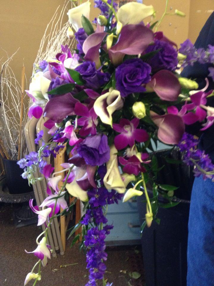 Cascading bridal bouquet of orchids, lark, callas etc