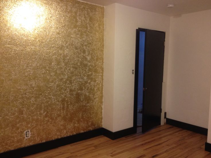 Gold glitter wall and black baseboards