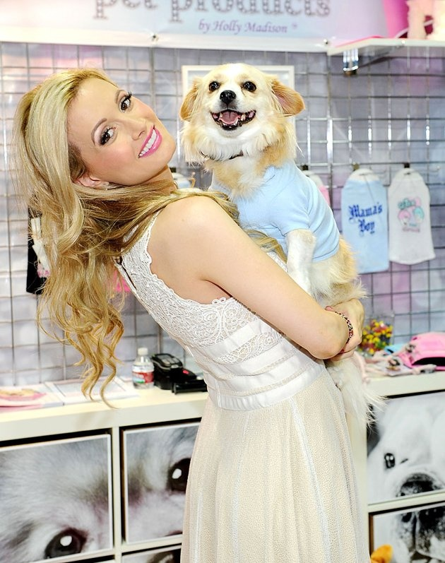 """mom-to-be Holly Madison is set to leave her gig in the Vegas revue """"Peep Show"""" (because, apparently, people who buy tickets to a """"striptease spectacular"""" aren't interested in seeing a pregnant woman on stage), she's gotta make a living another way. The 32-year-old launched her line of Lucky Pet Products by Holly Madison at the SuperZoo 2012 Convention at the Mandalay Bay on Tuesday, accompanied by her pooch Louis."""