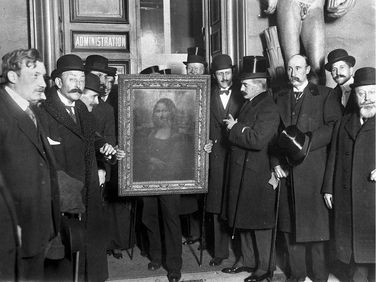 Officials gather around Leonardo da Vinci's 'Mona Lisa' (aka 'La Gioconda' or 'La Joconde') upon its return to Paris, 4th January 1914.