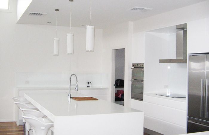 White kitchen, stone bench, false ceiling, kitchen island, stainless steel range hood, undermount sink