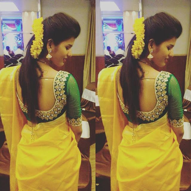 Bright yellow silk saree with plain border, dark green maggam and kundan work floral blouse with very broad neck patterned. Small beads an...