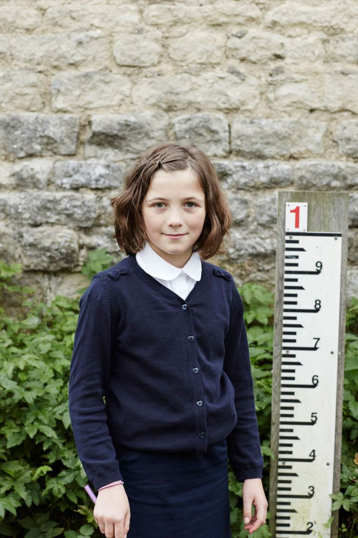 Portrait of girl in school uniform stands by water depth measure in front of stone wall.