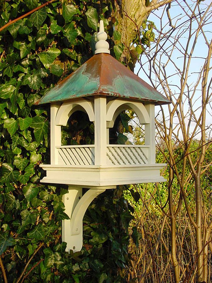 This stunning wall mounted bird table feeder makes a lovely giftThis attractive bird table can be fixed to walls, posts or trees using the included bracket and can easily be removed for cleaning. A larger version of the popular 'Hanging Bempton', this ornate and beautifully designed bird table will enhance any garden or outdoor environment. Superbly constructed from FSC timber, the intricate woodwork is painted in distressed pastel green, while the verdigris copper roof takes on a green…