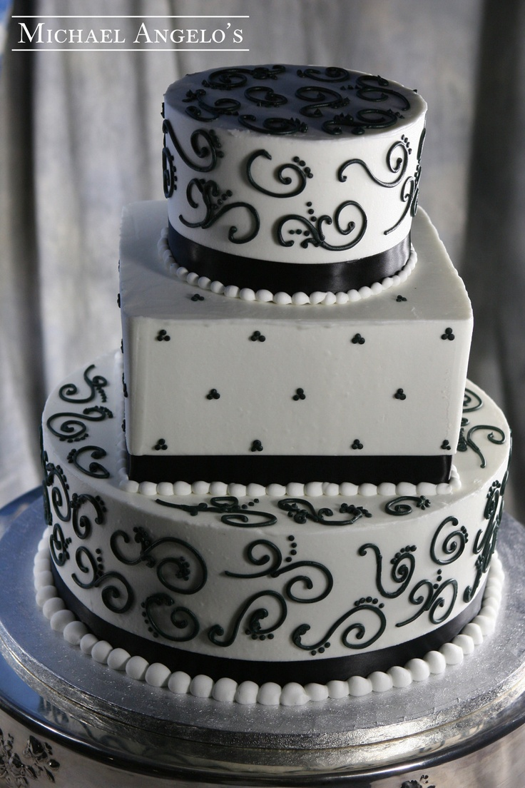 Mid-Square & Swirl #55Ribbons This cake is two round layers with a square shaped layer in between. The classic black and white color give this cake the perfect wedding look. A topper or fresh flowers can be added to bring in some color.