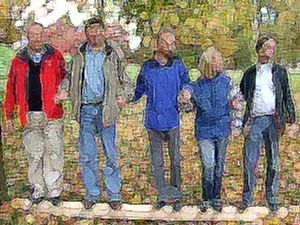 """Die Teilnehmer dieses Outdoor Moduls """"Teambalken"""" stehen in beliebiger Reihenfolge nebeneinander auf einem Balken oder einem horizontal liegenden Baumstamm."""